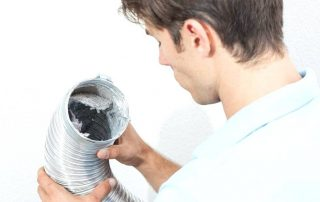 man looking into a dryer vent hose